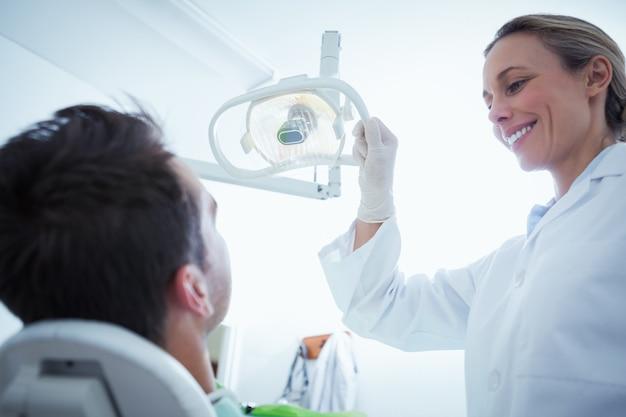 Feminino dentista examinando equipa os dentes