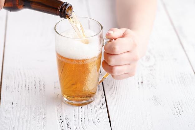 Feminino derramar cerveja na caneca de vidro, relaxar o conceito