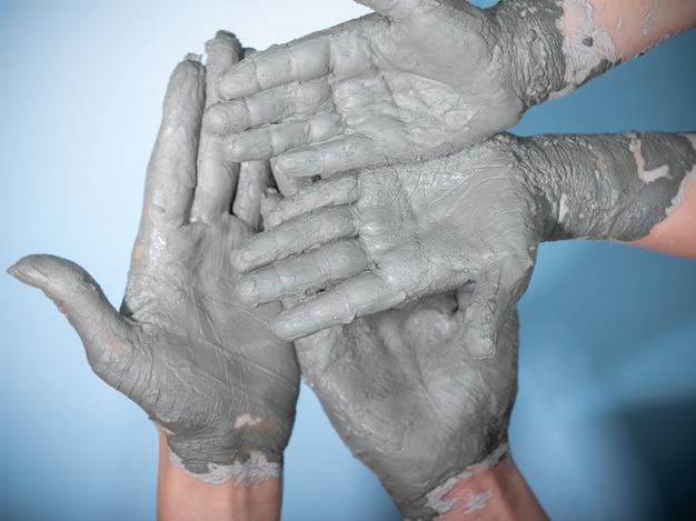 Feminino e criança trabalha com argila, mãos de artesão close-up,