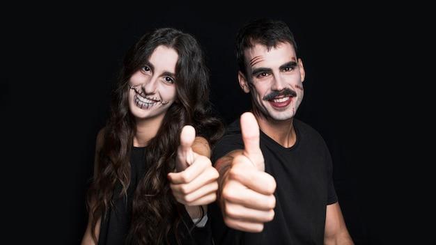 Feminino e masculino com maquiagem assustadora, colocando os polegares para cima