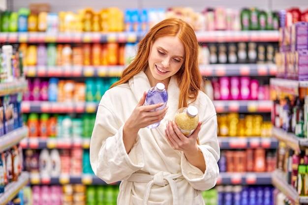 Feminino está comparando sais de banho no departamento de utensílios domésticos, escolha o melhor produto. mulher ruiva no roupão gosta de fazer compras