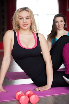 Feminino faz exercícios físicos em tapetes na classe de fitness