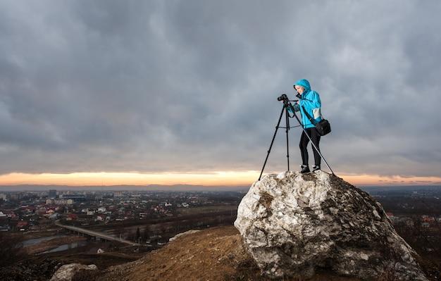 Feminino fotógrafo está de pé com a câmera no tripé na grande rocha