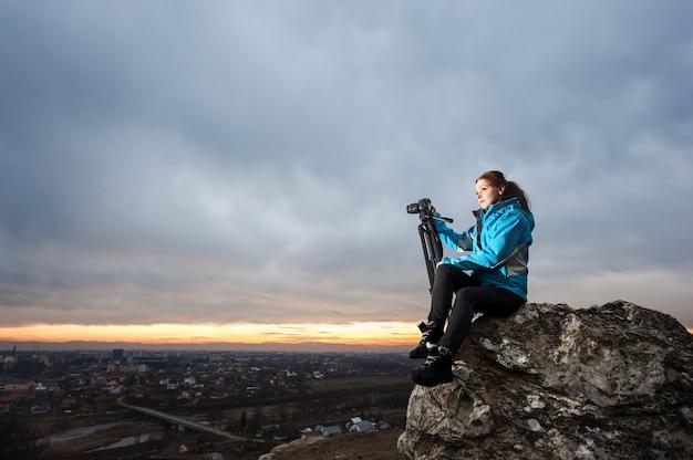Feminino fotógrafo sentado na pedra grande no ponto de visão geral da cidade no ocaso com a câmera no tripé