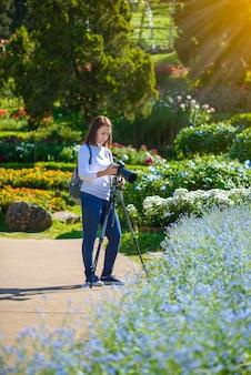 Feminino fotógrafo tirando fotos de flores