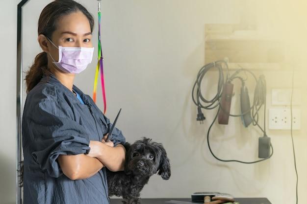 Feminino groomer segurando uma tesoura de corte para cães e gatos em um salão de beleza para animais de estimação
