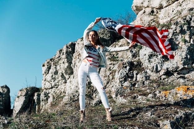 Feminino, levantando as mãos com bandeira na montanha