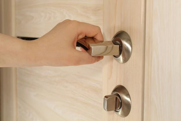 Feminino mão abre a porta de madeira