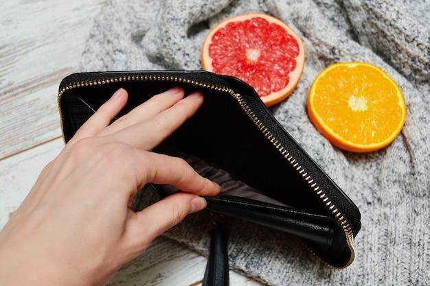 Feminino mão abrir bolsa vazia, frutas cítricas e uma camisola
