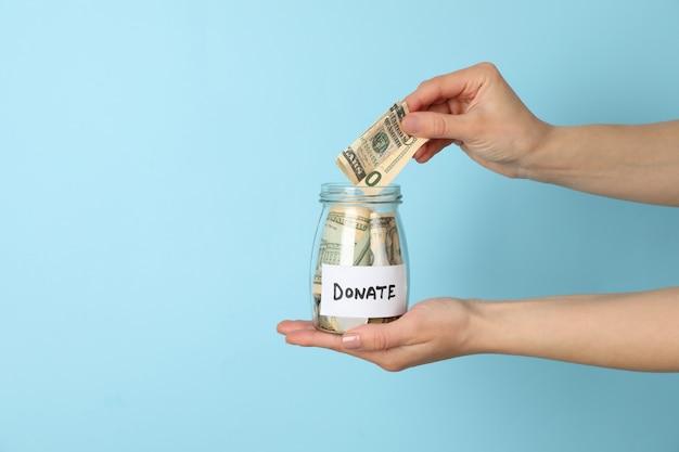 Feminino mão coloca dinheiro em frasco de vidro no espaço azul