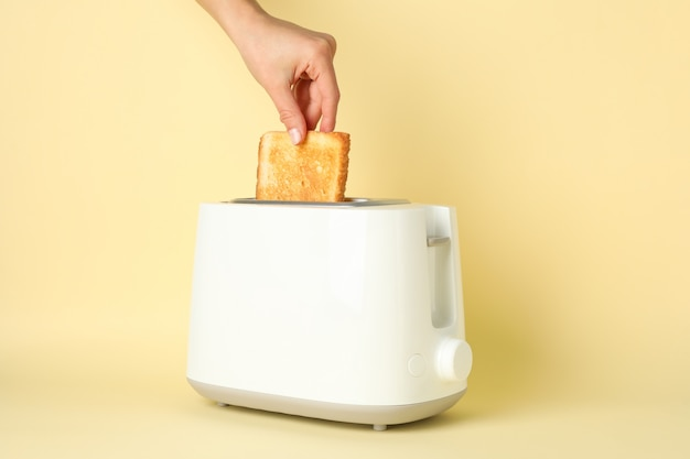 Feminino mão coloca pão em uma torradeira em fundo bege, espaço para texto