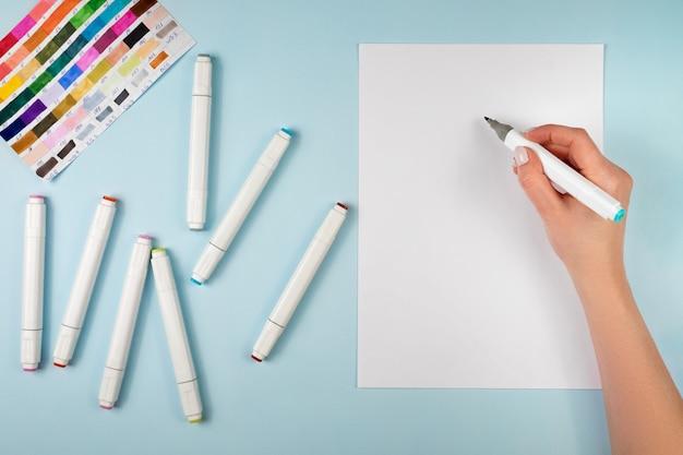 Feminino mão com marcador para desenho, fundo azul.