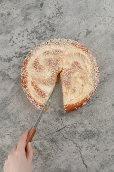 Feminino mão cortando a torta de maçã com a faca na superfície de mármore.