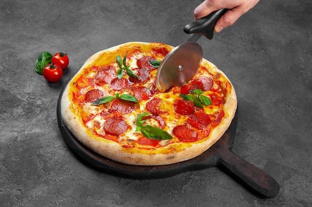 Feminino mão corte a fatia de pizza de calabresa com manjericão