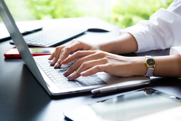 Feminino mão digitando no teclado do laptop