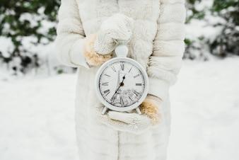 Feminino mão em um branco de malha luvas segurando grandes relógios em fundo de inverno