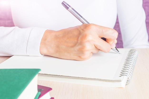 Feminino mão escreve no caderno por caneta.