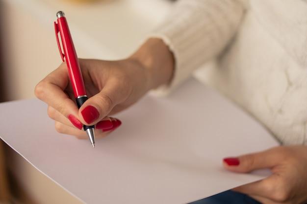 Feminino mão escrevendo em uma folha de papel
