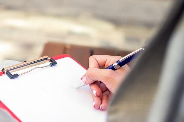 Feminino mão escrevendo no papel em branco