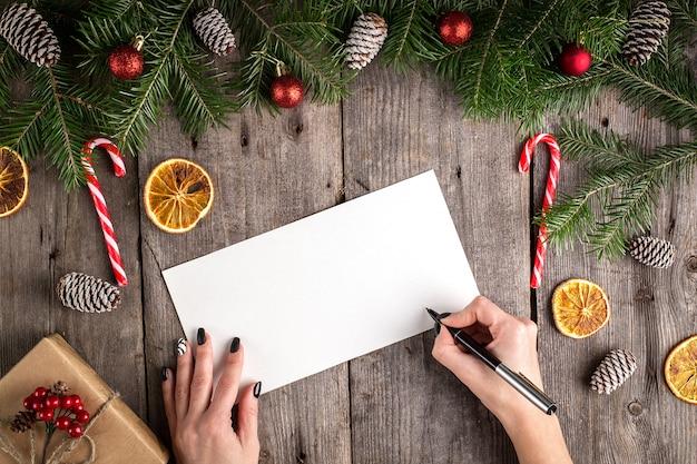 Feminino mão escrevendo uma carta para o papai noel na mesa de madeira