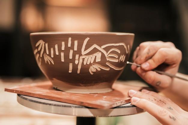 Feminino mão esculpindo na tigela de tinta