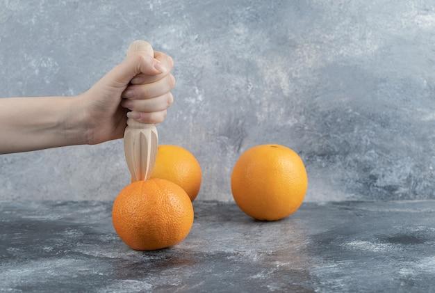 Feminino mão espremendo laranja na mesa de mármore.