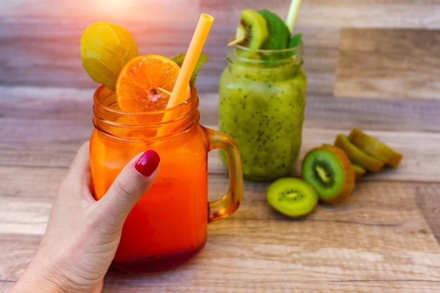 Feminino mão esquerda segurando uma fruta saudável com suco de laranja em cima da mesa