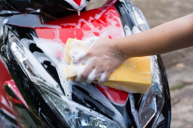 Feminino mão lavando uma motocicleta.
