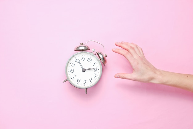 Feminino mão leva despertador em fundo rosa.