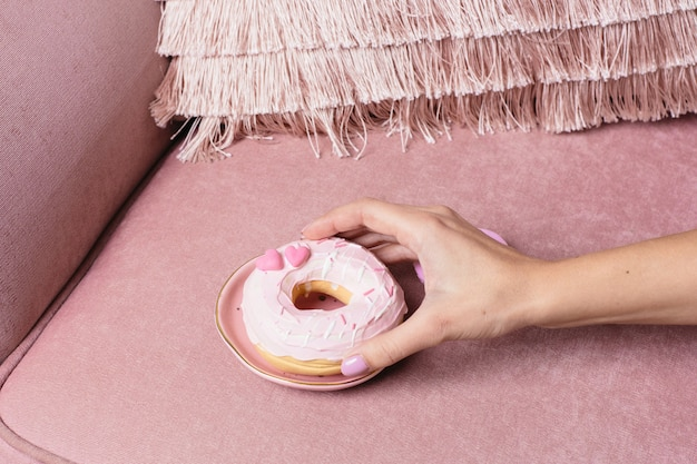 Feminino mão leva uma rosquinha rosa doce em uma superfície rosa