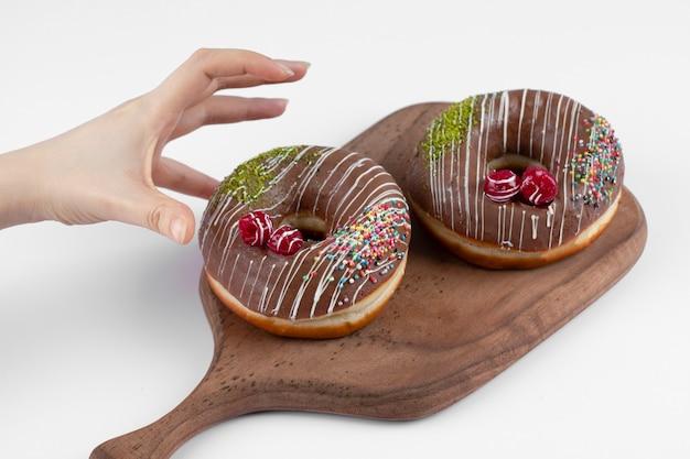 Feminino mão levando deliciosos donuts de chocolate em uma tábua de madeira.