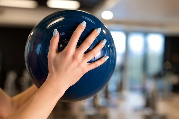 Feminino mão na academia com medball