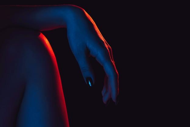 Feminino mão no joelho perto com luz de neon