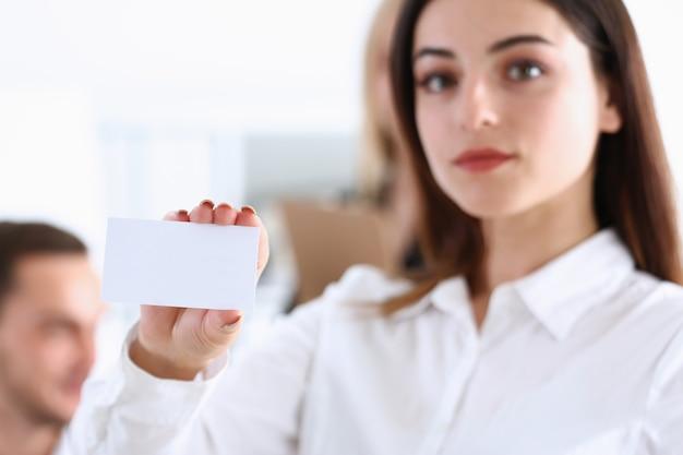 Feminino mão no terno dá cartão de visita em branco ao visitante