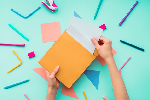 Feminino mão removendo o cartão do envelope sobre os acessórios de papelaria