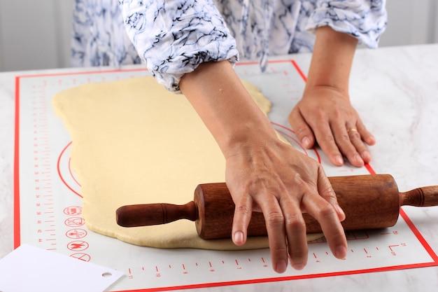 Feminino mão rolada pizza ou massa de pão com um rolo sobre uma mesa branca, polvilhada com farinha. cozinhar passo a passo na cozinha