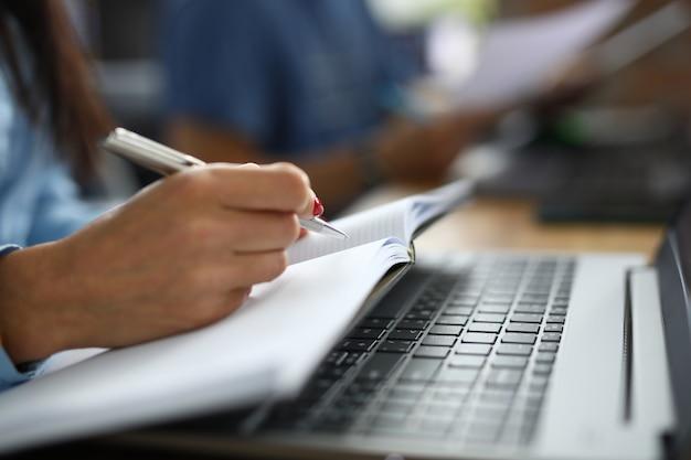 Feminino mão segura a caneta com notebook closeup