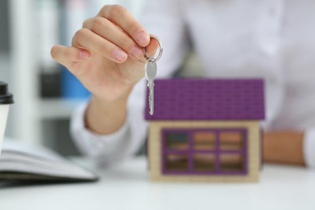 Feminino mão segura a chave da fechadura