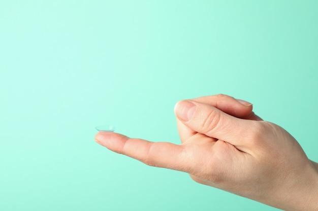 Feminino mão segura a lente de contato na superfície de hortelã, espaço para texto