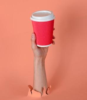 Feminino mão segura a xícara de café de papel através do papel rosa rasgado. conceito minimalista