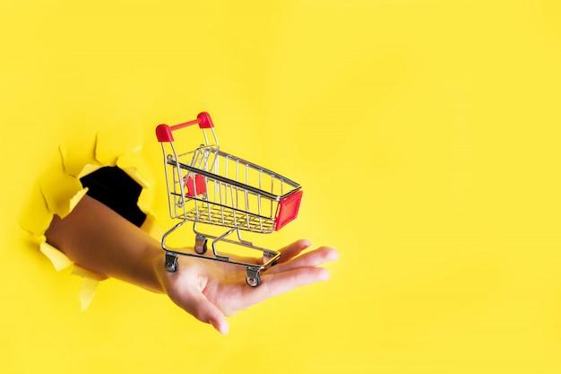 Feminino mão segura através de um buraco um carrinho de compras de supermercado mini em um papel amarelo. conceito de vendas