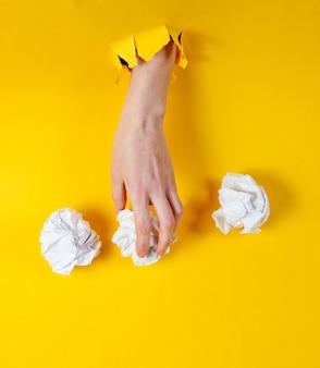 Feminino mão segura bolas de papel amassadas através de papel amarelo rasgado. conceito de negócio de ideia minimalista