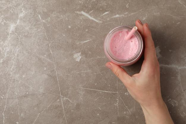 Feminino mão segura copo de milk-shake de morango em cinza