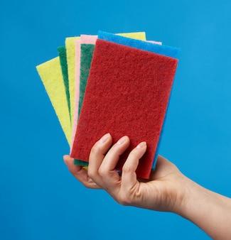 Feminino mão segura esponjas de cozinha de pilha para lavar a louça