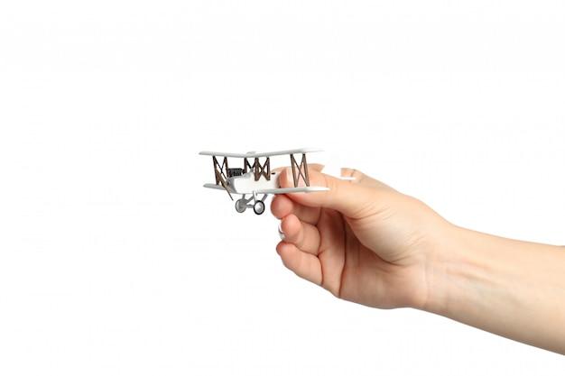 Feminino mão segura o avião de brinquedo, isolado no branco
