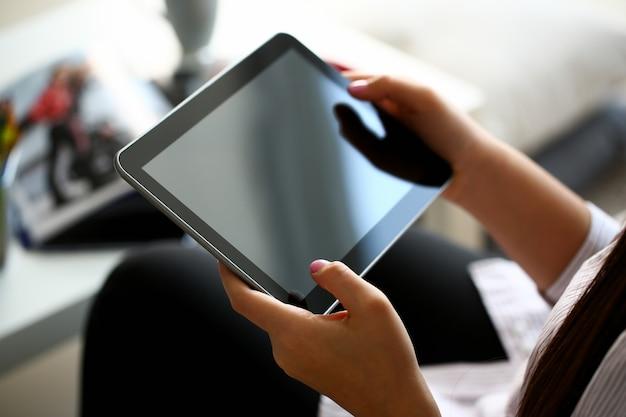 Feminino mão segura tablet em ambiente doméstico enquanto