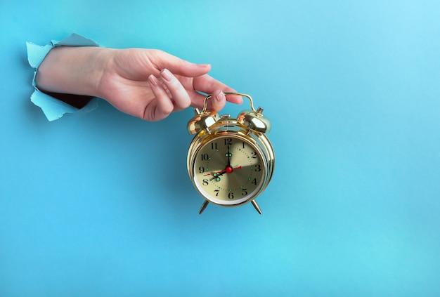 Feminino mão segura um despertador dourado através de um buraco em um fundo azul., conceito de tempo