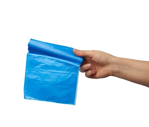 Feminino mão segura um pacote de sacolas plásticas azuis para lixo