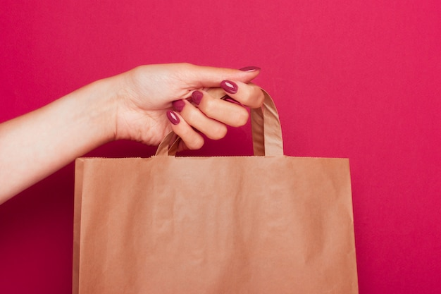 Feminino mão segura um saco de papel artesanal pelas alças
