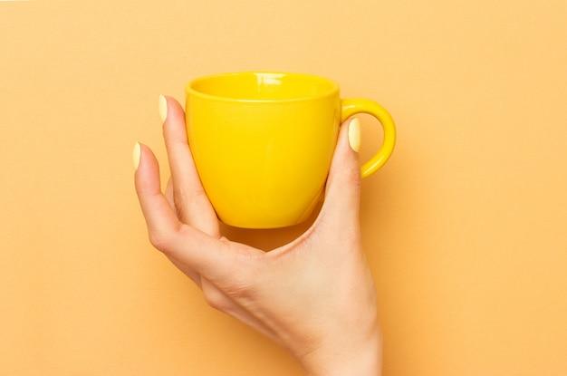Feminino mão segura uma caneca de cerâmica amarela para café e outras bebidas